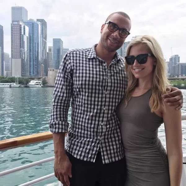 Aaron Hines is half embracing his girlfriend Kristine Leahy. They are wearing sunglasses and smiling. In the background, there are tall buildings.