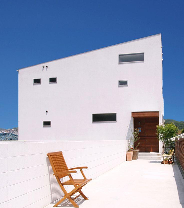 海と山を望む高台にある白い家