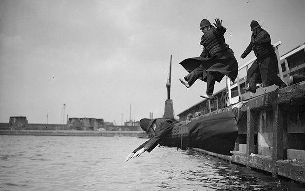 Plunging Policemen, July 9, 1935 Three fully clothed members of the Port of London Authority Police jump into the West India Docks during the annual test of their life jackets. Originally each dock company provided their own police force, with the West India Dock Company employing 100 men for this purpose. When the PLA was formed in 1909, the police forces still in existence (from London & India, Surrey Commercial, and Millwall docks) combined to form the PLA Police Force.