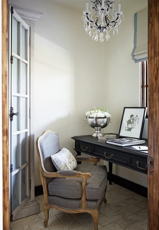 Small French office features a crystal chandelier over a black French desk, placed below windows dressed in a blue grosgrain roman shade, paired with a gray bergere chair lined with a gray damask pillow.