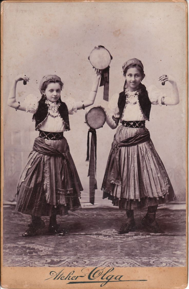 Olga Sudio - Two girls dancing and playing tambourines. They appear to be gypsies and are wearing traditional ethnic clothing, Oravicza, Romania.