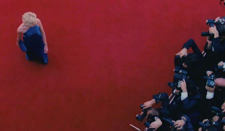 Naomi Watts como Diana. Direção fotográfica genial: vestido azul contra tapete vermelho, dialogando com a bandeira britânica.
