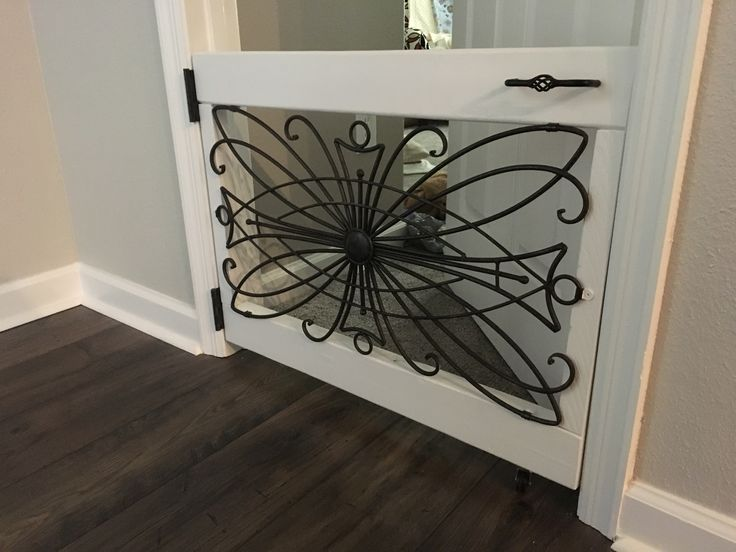 Pet gate door I made for my sewing room. The iron scroll came from Hobby Lobby. The wood frame has 4.5 inch lag screws and L brackets to support the corners. The handle and the hinges are from Habitat for Humanity Restore sprayed to match my doorknobs. I have a wheel on the to keep it from sagging. I also installed a magnetic latch to keep it closed.