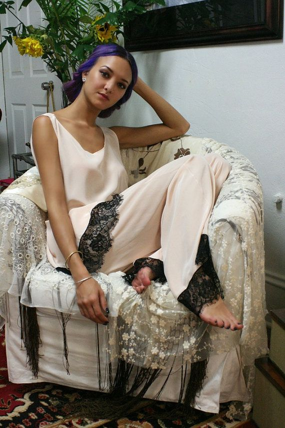 Blush silk pajamas. 20s flapper, Great Gatsby, Old Hollywood glam, all eras of flamboyance, risque behavior and starlit romance. Our 2015 Collection spawns from all of the above bringing new life to classic silhouettes. The Clara Pajama is 100% silk in soft rose blush. Loose tank style top very reminiscent of 20s flapper paired with a wide leg stove top pant. Stunning black lace trim runs around the bottom of tank and pajama pant as well as on the sleeves and bottom of the matching robe…