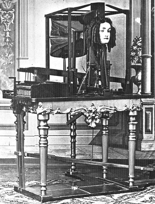 """The Euphonia, a mid-19th century gadget that could simulate human speech by pumping bellows-fed air over an artificial tongue set in a chamber of weird plates and valves. It had a severe woman's face and coils of hair in ringlets, and spoke in a """"weird, ghostly monotone."""""""