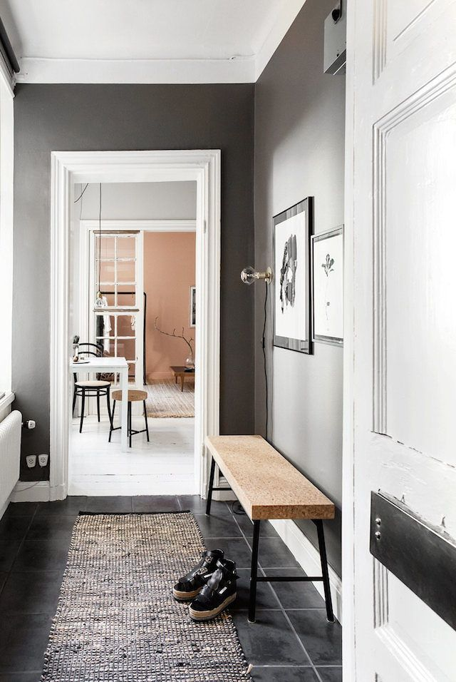 Dark grey wall and cork bench in the hallway of a small Stockholm pad