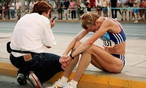 Paula Radcliffe sits on the curb after pulling out of the women's marathon