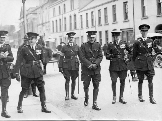 "RUC, Special Constabulary C1 Division. The men with the ""open collar"" tunics and armbands are members of the C1 Special Constabulary.  The man on the far right is Lt Col S E S Fitz-Simon, ex intelligence officer with 14th Royal Irish Rifles, later General Staff.  I believe the photo may have been taken on 8th April 1923 when they were inspected at Ormeau Park, Belfast by The Earl of Derby."