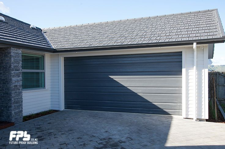 GRANGE SECTIONAL GARAGE DOOR from Garador (www.garador.co.nz).  The insulated door keeps the garage warmer in winter and cooler in summer. A great benefit if this homeowner wants to utilise the garage as another room in future. The wide raised pattern design of the Garador Grange, adds a horizontal dimension to any opening. Its distinctive wood grain finish offers the look and feel of timber with all the advantages of high grade Zinc-based steel.