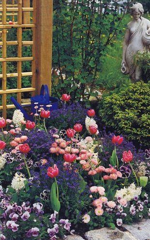 Весна Маленькая клумба в романтических красках возле террасы создает весеннее настроение. Лиловые фиалки, розовые маргаритки, голубые незабудки и белые гиацинты - любимцы этого сезона. А над ними своими ярко-розовыми головками покачивают тюльпаны.