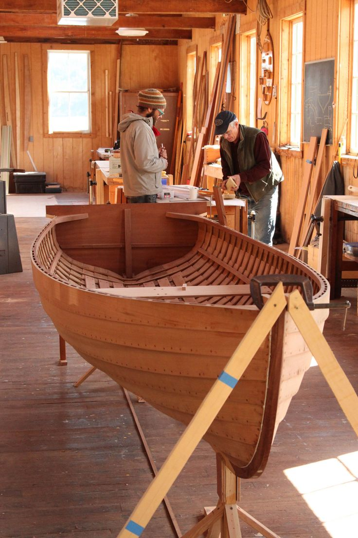 A quiet moment one morning before classes begin in the McPherson Shop with senior instructor Jeff Hammond and student Allan Fletcher. The boat in the foreground is a 14-foot Grandy skiff. You can see that it's inwales, riser and quarter knees are in place, and that one of the thwarts has been installed. The stern sheets are not yet in place. This boat was completed by Jeff's section in mid-June, 2012. It was picked up by its owner who had commissioned the boat. The boat is used on Lake C...