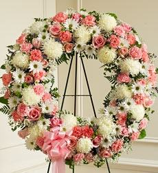 "Serene Blessings Standing Wreath - Pink & White - Large. This Standing Wreath is a beautiful reflection of your love and sympathy. Pink and white flowers such as roses, alstroemeria, carnations and more Accented by baby's breath, salal, heather and more Sent directly to the funeral home by family, friends and business associates Our florists use only the freshest flowers available so colors and assortment may vary Available in Large and Small sizes Large measures approximately 34""H x 34""W…"