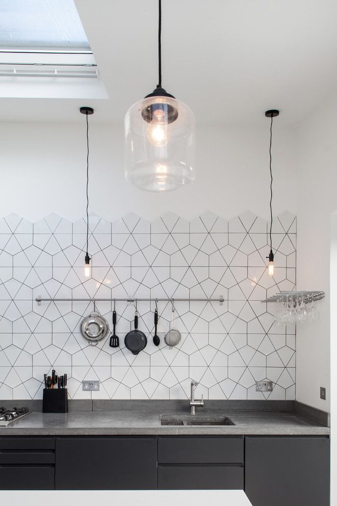 hexagonal tiles in the kitchen are pretty. Like the hanging lights too. Dark cabinets are probably easy to keep looking clean.