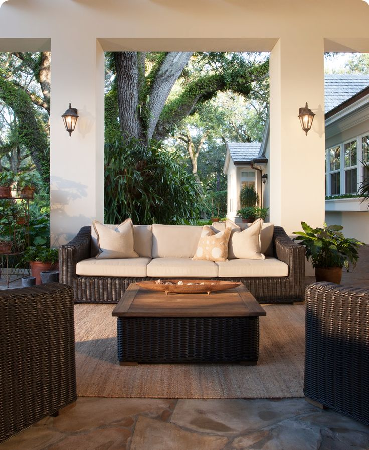 Create an outdoor living room with a weatherproof wicker sofa, coffee table, and area rug.