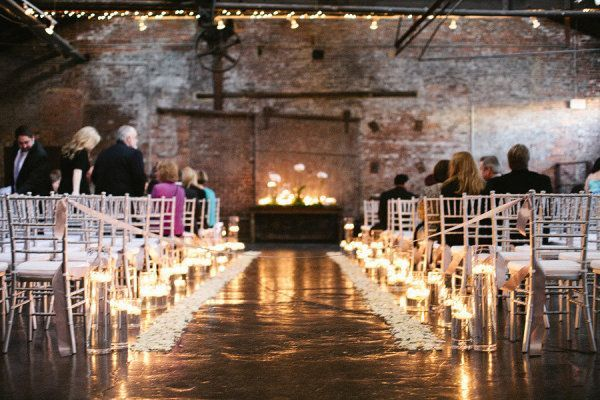 Candles line the aisle way in this industrial chic space