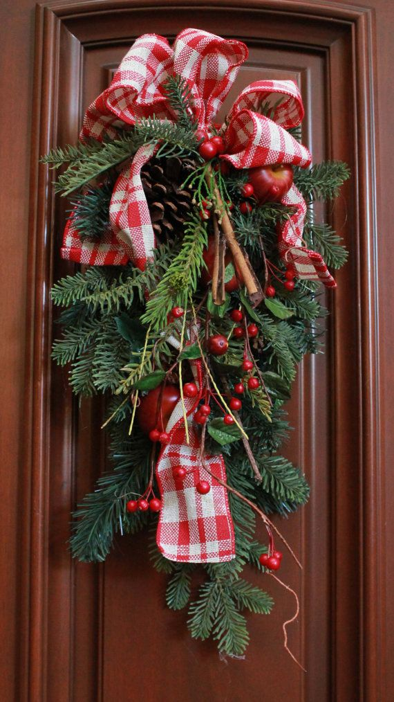 Brighten up your holiday with this beautifully arranged and decorated holiday swag. The perfect decoration to make any wall or door festive for the holidays!  This unique swag is adorned with red and white plaid ribbon, leaves, berries, twigs, pinecones, cinnamon sticks, and apples..  Approximate Dimensions: Hangs in Length- 19 Across in Width- 9 Depth- 4  *Please remember that all my items are creatively designed, arranged and decorated by hand so they are not always perfect in terms of…