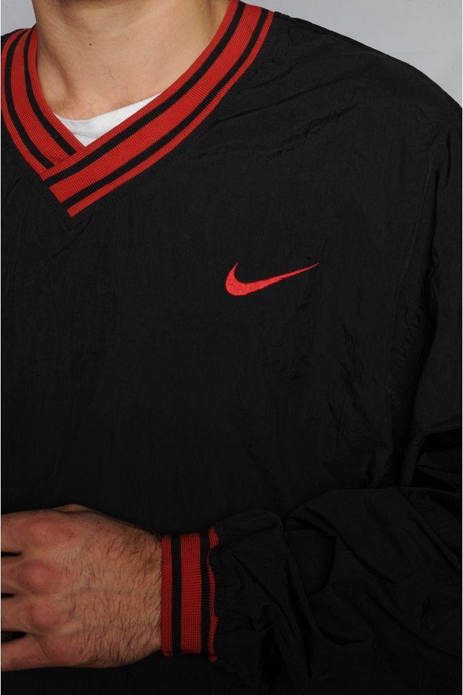 This Nike pullover windbreaker features red striping on the v-neck, hem, and cuffs with their logo embroidered on the left chest.