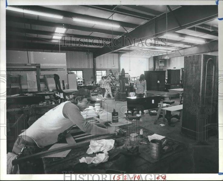 1985 Press Photo Eric Smith Sanding Furniture Headboard With Dark Stain.