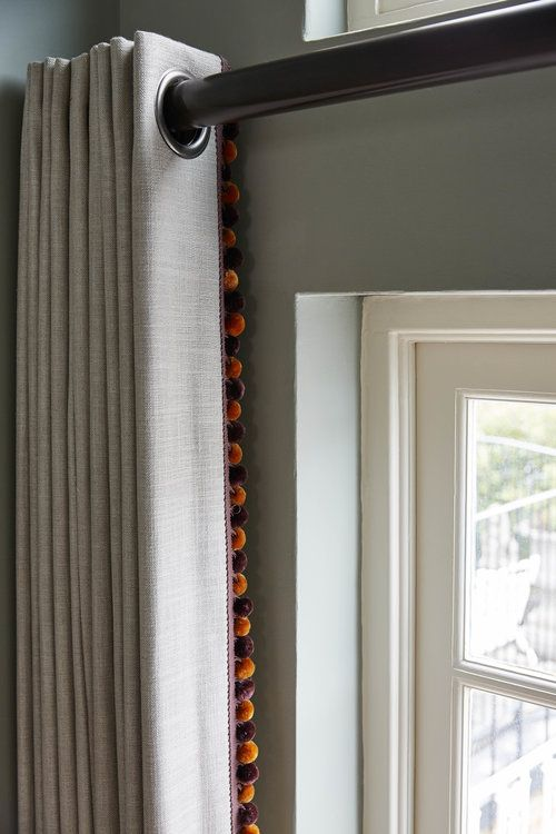 Simple eyelet curtains in a neutral linen with orange pompom trim to add a bespoke detail