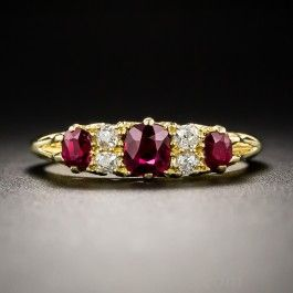 From early twentieth century Great Britain, crafted in rich 18ct. gold, a late-Victorian classic featuring a trio of vibrant red Siamese (Thai) rubies, totaling a .90 carat, interposed with pairs of small white and sparkling old mine-cut diamonds, and finished with a graceful scrolled gallery. An elegant vintage jewel, currently ring size 5 1/4.