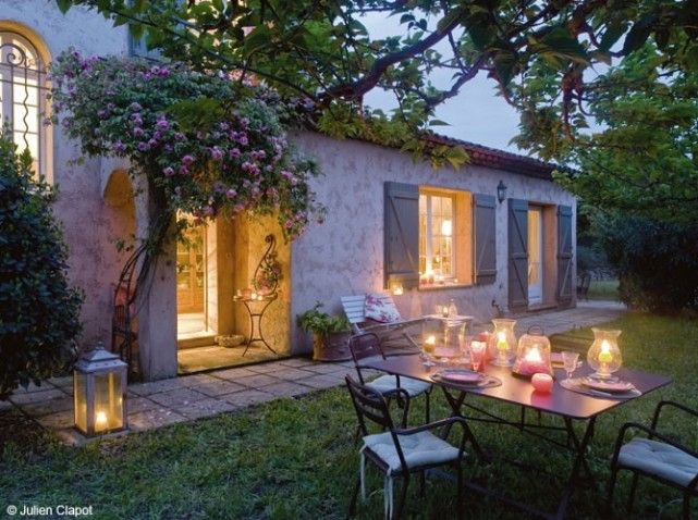 Country home in French Provence, tile roof, exterior shutters, patio table with chairs, trees: