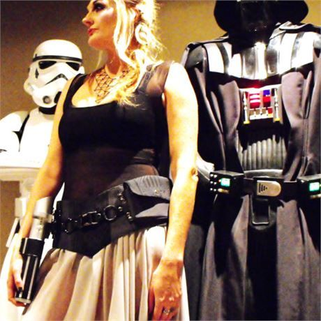 An awesome sci-fi inspired corset-style hip belt! Express your individual FORCE! To be worn resting on your hips, ready for action! In steel grey, with plenty of black accents, metal hardware, and a terrific chrome buckle. Although the buckle is functional in itself, in this design it is decorative only. Your clip and lightsaber (not included) can be attached to the removable webbing belt, which is secured to the rings in the back with metal snaps. Two pockets with velcro closure are…