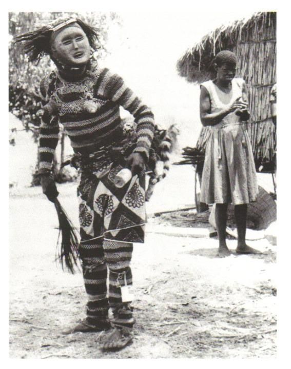 """Field photo from a 1920's post card featuring a Lwena Pwevo/Pwo performer holding a flywhisk and hand rattle made from a tin can. The mask dances with the women who clap and sing to musically accompany the performer. Photo from Baltimore Museum of Art From """"CHOKWE! - Art and Initiation Among Chokwe and Related Peoples"""". Relates to Female (Pwo) mask. Chokwe peoples (Democratic Republic of the Congo). Late 19th to early 20th century C.E. Wood, fiber, pigment, and metal."""