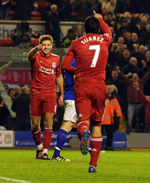 Steven Gerrard and Luis Suarez salute each other after Gerrard's hat-trick goal in the Merseyside derby.