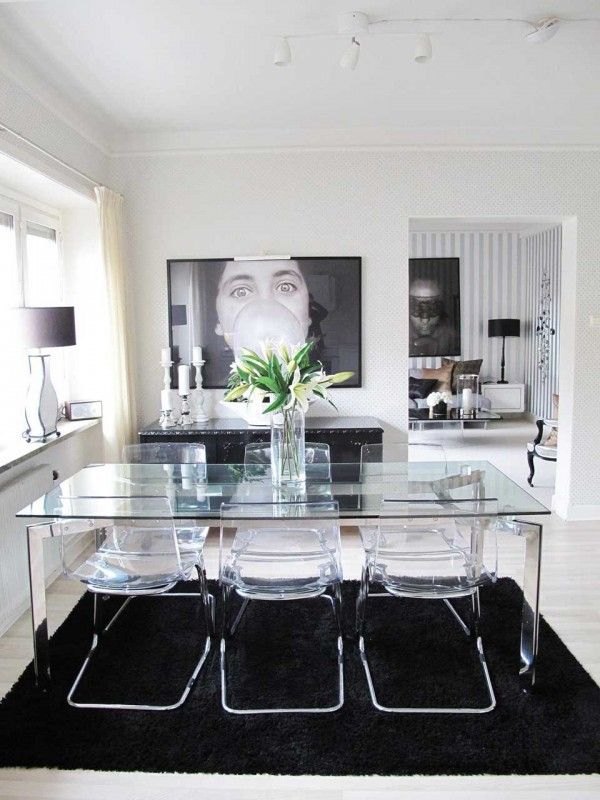 Glass dining table and acrylic chairs with black & white design elements