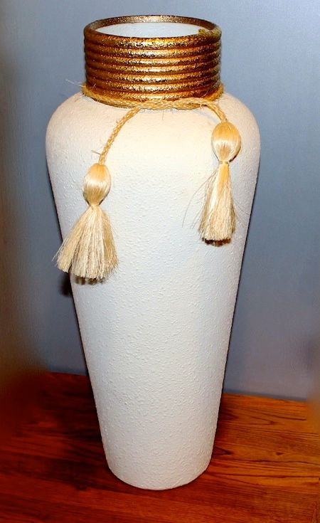 """Vase with Tassels -  Standing 21"""" tall x 10"""" across...the body has a texture...is light beige the neck is gold w/ tassel  Order # V-101..$50"""
