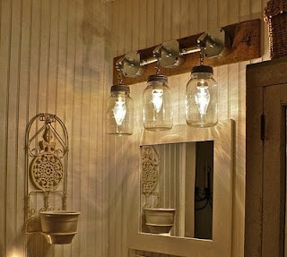 Mason jar bathroom light. Could take existing lighting, attach to reclaimed wood and add the jars, hmmmmm...wheels turning!