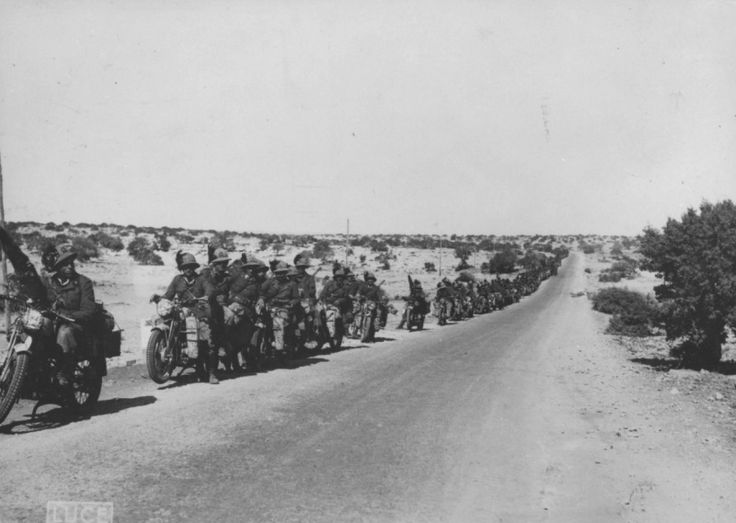 Column Italian Bersaglieri motorcyclists during a stop on the road in North Africa.