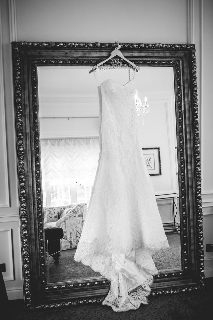 Wedding dress hanging on mirror.Photographed by JMGant Photography…