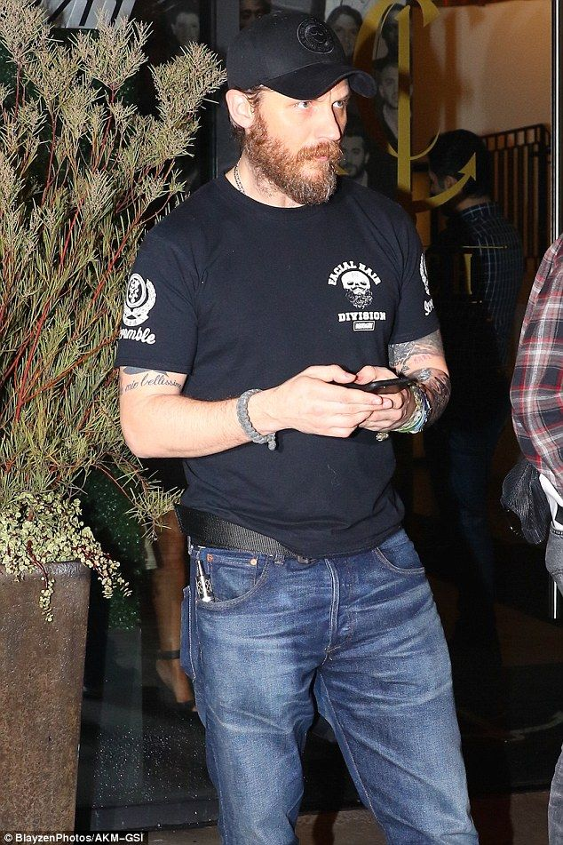 Pensive: The 39-year-old failed to raise a smile as as he checked his phone outside the restaurant after a boy's night out at Catch