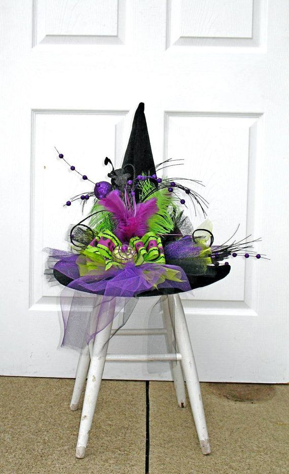 Black Felt witch hat adorned with a row of designer ribbon and tulle, clusters of purple pumpkins, feathers and silk sprigs. Great hat for a