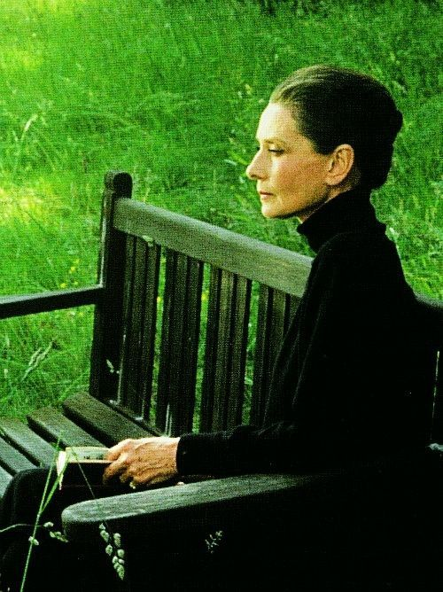 A fabulous photo of an older Audrey Hepburn reading a book and reflecting.