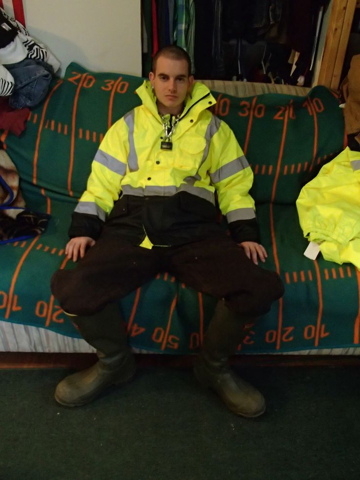 Reflective jacket with his pants shoved inside a mighty big pair of rubber boots
