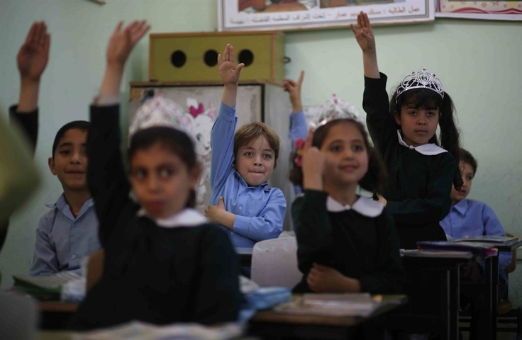 ISLAM - Palestinian school children raise their hands during a class in al-Qahera elementary school in Gaza City on April 2. New rules from the Education Ministry of the Islamist Hamas movement ruling the Gaza Strip will bar men from teaching at girls' schools and mandate separate classes for boys and girls from the age of nine.