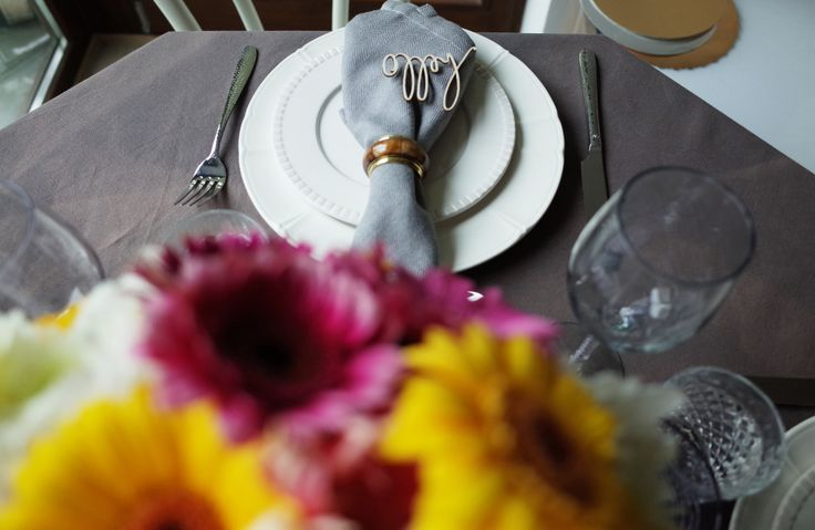 Gerberas and white plates with decor. Gray napkins and tableware