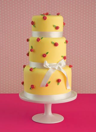 A zesty yellow with pretty pink rosebuds for a sensational modern wedding cake with a retro vibe.
