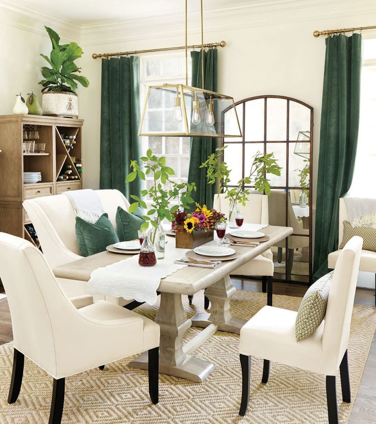 Rich, emerald green velvet drapes give this neutral dining room a chic look.