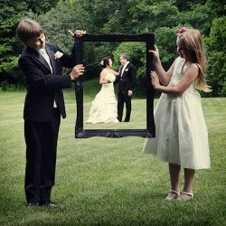 so cute to have the ring bearer and flower girl hold a picture frame in front of the bride and groom for a cute wedding day picture.