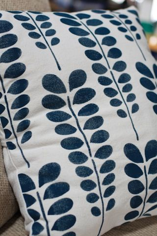 How to use fabric paint and drop cloths to create custom couch pillow covers.