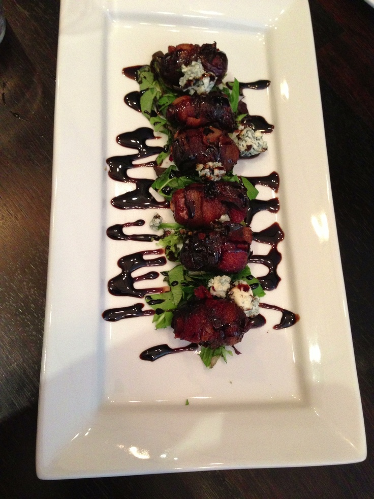 Toasted Almond stuffed date wrapped in bacon over arugula with ...