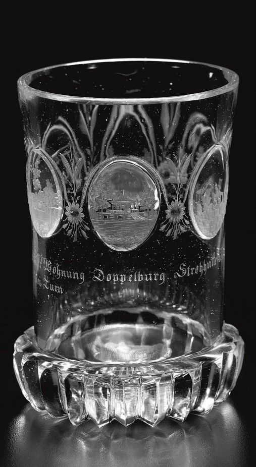 A Bohemian beaker with views of Teplitz dated 1827 the slightly waisted cylindrical form cut with six small oval medallions, each engraved with views of buildings, individually inscribed below Gärtner Wohnung bei Turn, Doppelburg, Strohhütte bei Turn, Garten Tempel and Garten Saal, one medallion inscribed Teplitz 1827, each divided by stylised leaves and flowerheads, above a cogwheel foot and radial-cut base 11.8cm., 4 5/8 in.