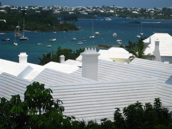 """To build a traditional Bermudian roof, masons mortar rectangular slabs, or ""slates,"" of local limestone to each other over a hip-roof frame. Then they apply more mortar over the top and edges of the slates, filling the joints and giving the roof its traditional stepped shape. Along the lower edges of the roof, they sculpt a long concrete trough for a gutter, which directs rainwater to a pipe that filters it and funnels it into a cistern buried alongside (or in the basement) of the house."""