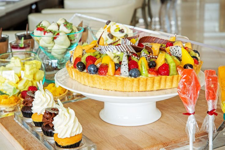 Fruit tarts, cupcakes and strawberry dipped in chocolate for high tea at Mulia Bali