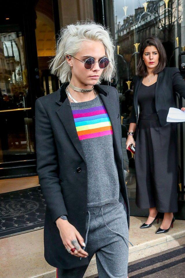 Cara DeLavigne usando blusa de arco iris cinza com calca de moletom, blazer e chockers