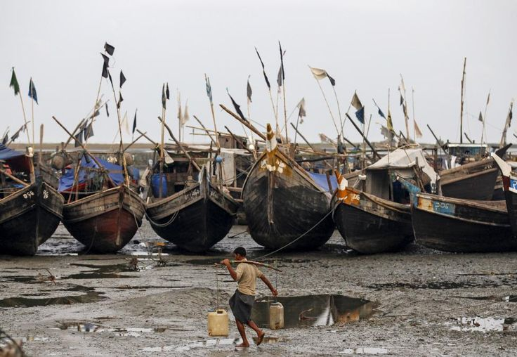 A Rohingya Muslim man carries containers of water in front of boats near a jetty at a refugee camp outside Sittwe, Myanmar May 21, 2015. Often beaten, and given little food and water, at least 50 Rohingya came back over the weekend after paying boat captains between $200 and $300 per person, people in one of the camps said. REUTERS/Soe Zeya Tun
