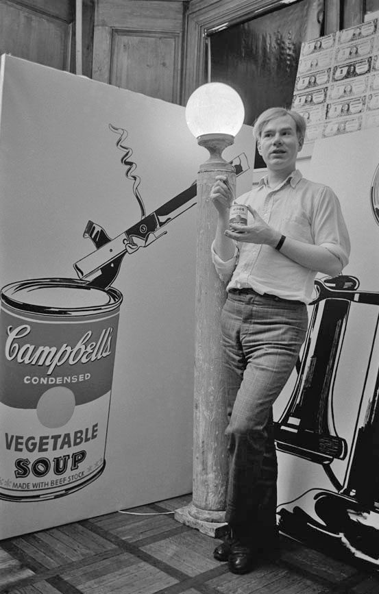 Andy Warhol at the Silver Factory posing with a Campbell Soup Can painting. Circa mid 1960's